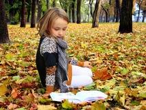 La chica joven lee un libro en el parque del otoño Imagen de archivo libre de regalías