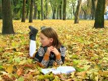 La chica joven lee un libro en el parque del otoño Fotos de archivo libres de regalías