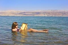 La chica joven lee un libro que flota en el mar muerto en Israel Fotos de archivo