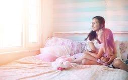 La chica joven lee a una chica joven del libro con una hija Imagen de archivo libre de regalías