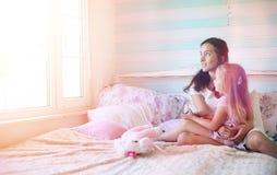 La chica joven lee a una chica joven del libro con una hija Imágenes de archivo libres de regalías