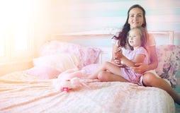 La chica joven lee a una chica joven del libro con una hija Imagen de archivo