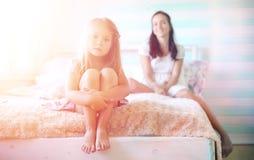 La chica joven lee a una chica joven del libro con una hija Foto de archivo