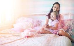 La chica joven lee a una chica joven del libro con una hija está sentando o Fotos de archivo libres de regalías