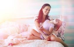 La chica joven lee a una chica joven del libro con una hija está sentando o Foto de archivo