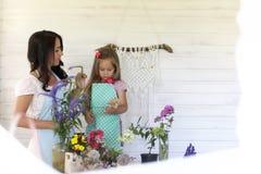 La chica joven lee a una chica joven del libro con una hija está sentando o Foto de archivo libre de regalías