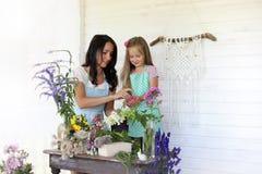 La chica joven lee a una chica joven del libro con una hija está sentando o Fotografía de archivo libre de regalías