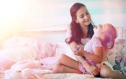 La chica joven lee a una chica joven del libro con una hija está sentando o Imágenes de archivo libres de regalías