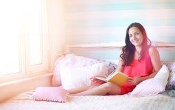 La chica joven lee a una chica joven del libro con una hija está sentando o Imagenes de archivo