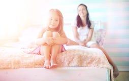 La chica joven lee a una chica joven del libro con una hija está sentando o Fotografía de archivo
