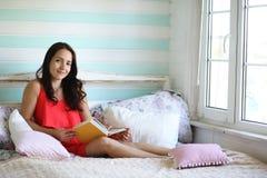 La chica joven lee a una chica joven del libro con una hija está sentando o Fotos de archivo