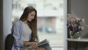 La chica joven leyó el libro que se sentaba en el travesaño de la ventana almacen de metraje de vídeo