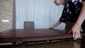La chica joven limpia en la cocina por la mañana limpia la tabla después de desayuno almacen de metraje de vídeo