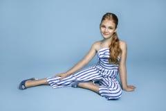 La chica joven linda con el pelo rubio largo se vistió en un equipo rayado blanco y azul que se colocaba en un fondo blanco Fotos de archivo libres de regalías