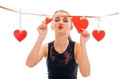 La chica joven linda envía beso y guarda la cinta con los corazones Imágenes de archivo libres de regalías
