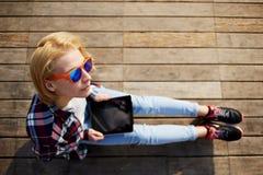 La chica joven linda pasa tiempo en el embarcadero y comprueba el correo fotografiado Imagen de archivo libre de regalías