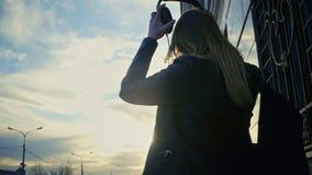 La chica joven linda pone los auriculares en parque en la oscuridad Fotografía de archivo
