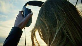 La chica joven linda pone los auriculares en parque en la oscuridad, cierre para arriba Foto de archivo