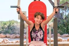 La chica joven linda que ejercita los brazos y el pecho en gimnasio trabajan a máquina al aire libre Imagenes de archivo