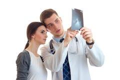 La chica joven linda que se coloca al lado de un doctor en una capa y él blancos del laboratorio le muestra una radiografía Imagen de archivo