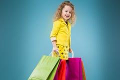La chica joven linda vistió todos en diversos bolsos del control amarillo Foto de archivo