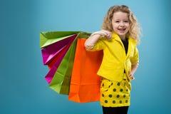 La chica joven linda vistió todos en diversos bolsos del control amarillo Fotos de archivo