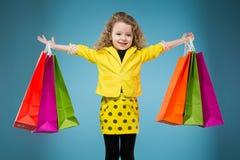 La chica joven linda vistió todos en diversos bolsos del control amarillo Imágenes de archivo libres de regalías