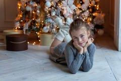 La chica joven miente cerca de un árbol de navidad Imagenes de archivo