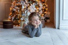 La chica joven miente cerca de un árbol de navidad Fotografía de archivo