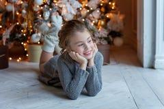 La chica joven miente cerca de un árbol de navidad Fotos de archivo libres de regalías