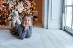 La chica joven miente cerca de un árbol de navidad Fotos de archivo
