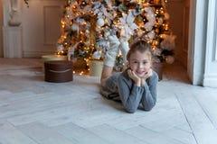 La chica joven miente cerca de un árbol de navidad Fotografía de archivo libre de regalías