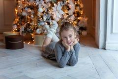 La chica joven miente cerca de un árbol de navidad Foto de archivo