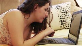 La chica joven miente en el sofá y esté charlando vía el ordenador portátil almacen de video