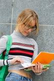 La chica joven mira el libro abierto que coloca la pared cercana Foto de archivo