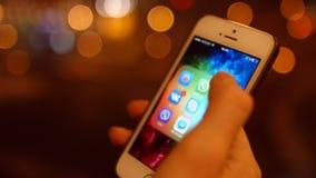La chica joven mira el primer de las fotos de los usos y de la mirada del teléfono móvil 4K 30fps ProRes metrajes