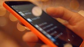 La chica joven mira el primer de las fotos de los usos y de la mirada del teléfono móvil 4K 30fps ProRes almacen de video