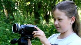 La chica joven mira en la cámara de vídeo en fondo del fondo verde del parque almacen de metraje de vídeo