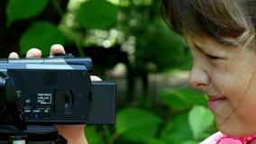 La chica joven mira en la cámara de vídeo en fondo del fondo verde del parque metrajes