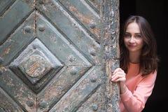 La chica joven mira hacia fuera de detrás la puerta de madera antigua Fotografía de archivo