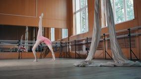 La chica joven modelo adolescente realiza agraciado la acrobacia en salón de baile Fotografía de archivo libre de regalías