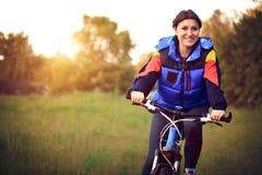 La chica joven monta una bicicleta en el campo Imágenes de archivo libres de regalías