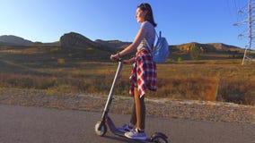 La chica joven monta una vespa eléctrica en el camino, sol