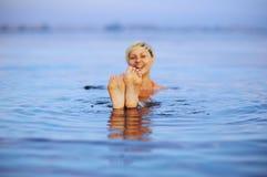La chica joven muestra dos piernas en superficie de la agua de mar Fotos de archivo