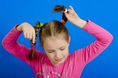La chica joven muestra dos trenzas Foto de archivo