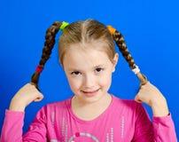 La chica joven muestra dos trenzas Foto de archivo libre de regalías