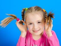 La chica joven muestra dos trenzas Fotografía de archivo