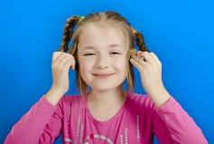 La chica joven muestra dos trenzas Fotos de archivo libres de regalías