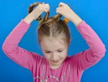La chica joven muestra dos trenzas Imagenes de archivo