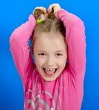 La chica joven muestra dos trenzas Fotos de archivo